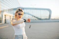 Vetri d'uso della donna bionda di affari che parlano gli orologi astuti immagine stock libera da diritti
