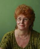 Vetri d'uso della donna di mezza età dai capelli rossi Fotografie Stock