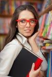 Vetri d'uso della giovane donna e tenere un libro Fotografia Stock
