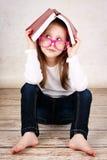 Vetri d'uso della piccola scolara annoiata e nascondersi nel libro immagini stock libere da diritti