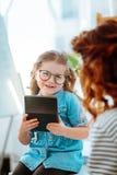 Vetri d'uso della ragazza che sorridono dopo il gioco con il calcolatore immagini stock libere da diritti
