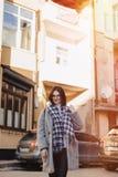Vetri d'uso della ragazza positiva attraente in un cappotto sui precedenti delle costruzioni sulle automobili fotografia stock