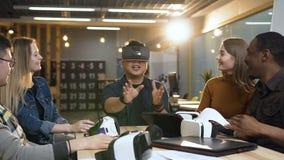 Vetri d'uso di realtà virtuale del giovane uomo cinese divertendosi giocando gioco mentre i suoi cowokers che lo ridono di video d archivio