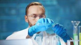 Vetri d'uso e guanti dello scienziato maschio medio del primo piano che lavorano nel laboratorio moderno archivi video