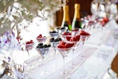 Vetri dei lamponi, fragole, more sulla barra del ghiaccio Cena di galà al ristorante immagine stock
