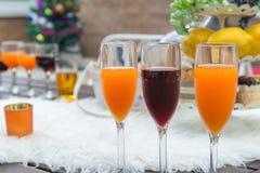 Vetri dei vini e del succo d'arancia sulla tavola per il partito di sera Immagine Stock