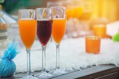 Vetri dei vini e del succo d'arancia sulla tavola per il partito di sera Immagine Stock Libera da Diritti