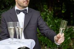 Vetri del champagne del servizio del cameriere su un vassoio Fotografie Stock Libere da Diritti