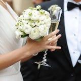 Vetri del champagne della holding dello sposo e della sposa Immagini Stock