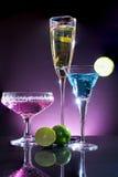 Vetri del cocktail blu, giallo e porpora con calce verde sulla t Fotografia Stock