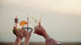 Vetri del tintinnio di divertimento delle mani con il cocktail urbano colorato di estate di vetro video d archivio