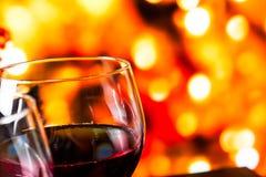 Vetri del vino rosso contro il fondo unfocused variopinto delle luci Immagine Stock Libera da Diritti