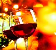 Vetri del vino rosso contro il fondo unfocused variopinto delle luci Fotografie Stock