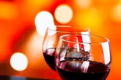 Vetri del vino rosso contro il fondo unfocused variopinto delle luci Fotografia Stock Libera da Diritti