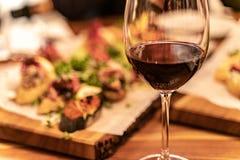 Vetri del vino rosso su una plancia di legno con il vassoio defocused di approvvigionamento dell'antipasto ai precedenti fotografia stock libera da diritti