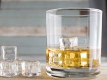 Vetri del whiskey con i cubetti di ghiaccio su vecchio legno Fotografia Stock