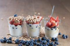 Vetri dell'albero in una fila in pieno di yogurt, delle bacche e del cereale più fotografia stock libera da diritti