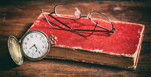Vetri dell'occhio e dell'orologio da tasca su un vecchio libro Immagini Stock Libere da Diritti