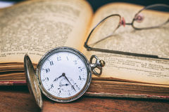 Vetri dell'occhio e dell'orologio da tasca su un vecchio libro Fotografia Stock