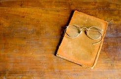 Vetri dell'oggetto d'antiquariato e libro di cuoio Immagini Stock