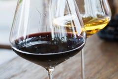 Vetri della fine del vino rosso e bianco su su fondo di legno Immagine Stock
