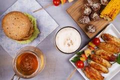 Vetri di birra con le ali di pollo, l'hamburger, le polpette, il cereale arrostito e le verdure Morsi della birra Fotografia Stock