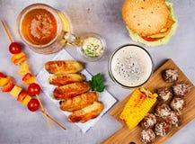 Vetri di birra con le ali di pollo, l'hamburger, le polpette, il cereale arrostito e le verdure Morsi della birra Immagine Stock Libera da Diritti