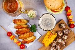 Vetri di birra con le ali di pollo, l'hamburger, le polpette, il cereale arrostito e le verdure Morsi della birra Immagini Stock Libere da Diritti