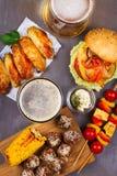 Vetri di birra con le ali di pollo, l'hamburger, le polpette, il cereale arrostito e le verdure Morsi della birra Fotografia Stock Libera da Diritti