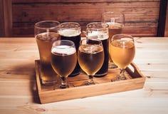 Vetri di birra e tazze di birra sulla tavola di legno Fuoco selettivo Fotografie Stock Libere da Diritti