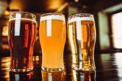 Vetri di birra leggera e scura su un fondo del pub immagini stock