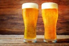Vetri di birra leggera fredda su un fondo di legno tonalità prescelto fotografie stock libere da diritti