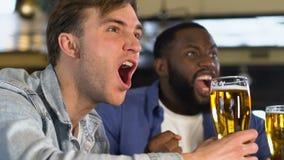 Vetri di birra tintinnanti degli uomini emozionali in pub, gioco di sorveglianza di sport, campionato stock footage