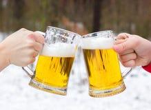 Vetri di birra tintinnanti sul fondo della foresta di inverno Fotografie Stock Libere da Diritti
