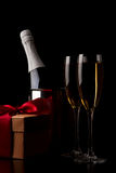 Vetri di champagne con i regali rossi del nastro Immagini Stock Libere da Diritti