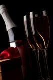 Vetri di champagne con i regali rossi del nastro Fotografie Stock