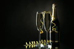 Vetri di champagne con la bottiglia sul nero Immagine Stock