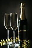 Vetri di champagne con la bottiglia sul nero Fotografie Stock