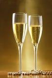 Vetri di champagne con la priorità bassa dell'oro fotografie stock