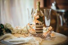Vetri di Champagne con una decorazione di nozze e una bottiglia di champagne Immagini Stock