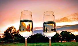 2 vetri di Champagne davanti ad un cielo rosso nei precedenti immagine stock