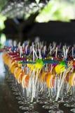 Vetri di cocktail con gli accessori variopinti: rotoli del cocktail, ombrelli del cocktail e fette arancio Fotografie Stock