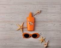 Vetri di colore arancio e di protezione solare su un fondo di legno Immagine Stock