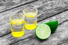 Vetri di colpo con la tequila messicana dorata con le fette della calce ed il sale sulla vecchia tavola di legno Fuoco selettivo  immagine stock