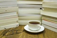Vetri di lettura con la tazza di tè e dei libri fotografia stock libera da diritti