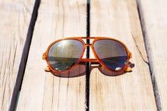 Vetri di sole arancio moderni con i vetri dello specchio isolati su un fondo di legno Fotografia Stock Libera da Diritti