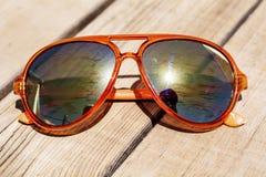 Vetri di sole arancio moderni con i vetri dello specchio isolati su un fondo di legno Fotografia Stock