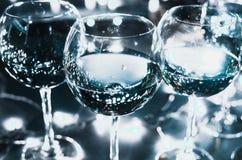 Vetri di vetro con vino sui precedenti delle ghirlande luminose Immagine Stock