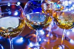 Vetri di vetro con vino sui precedenti delle ghirlande luminose Immagine Stock Libera da Diritti