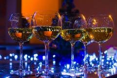 Vetri di vetro con vino sui precedenti delle ghirlande luminose Fotografia Stock Libera da Diritti